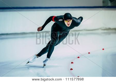 beautiful male skater during race sprint distance along path of ice Palace