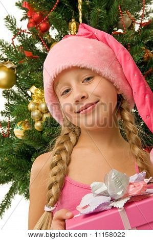Happy Santa girl near the christmas tree