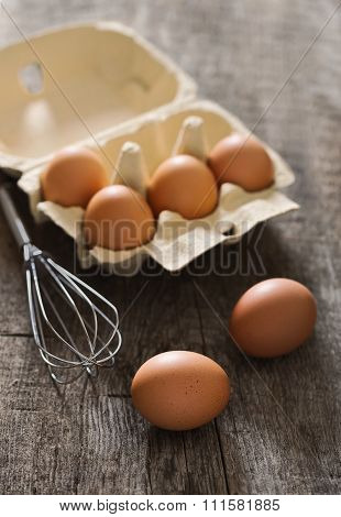 Composition with brown eggs and whisk on the old rustic backgrou