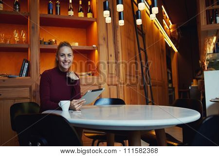 Happy European woman posing while sitting with touch pad in comfortable coffee shop interior