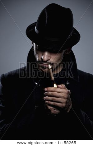 Mysterious man in hat lighting a cigarette