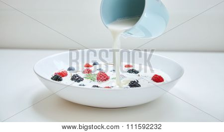 Milk Spoil From Blue Cup To Muesli In White Plate