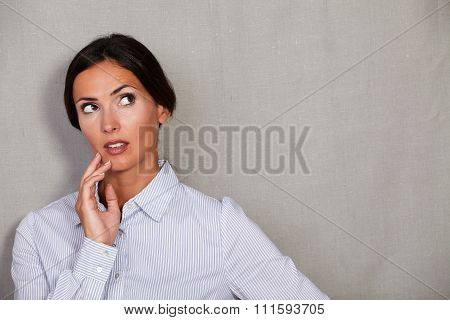Well-dressed Female Looking Away With Hand On Chin