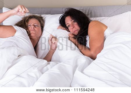Two Attractive Women Waking Up Next To Each Other In Bed