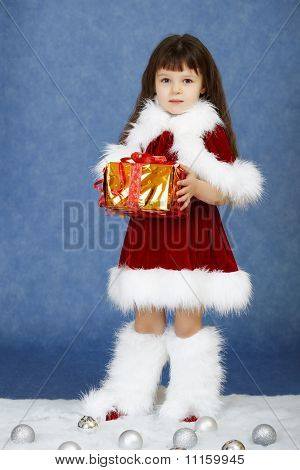 Little Girl In Fur New Year's Clothes With Gift