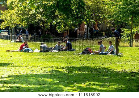 Young People Is Resting On The Grass  St. James Park In London.