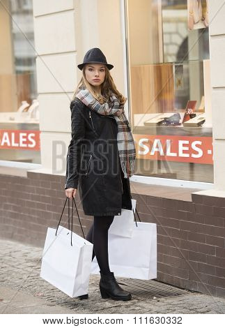 Fashion Woman With Hat And Scarf Near A Window Shop
