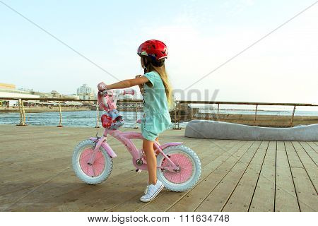 Little blond caucasian girl riding on pink bicycle on the jetty by the sea and look at the horizon
