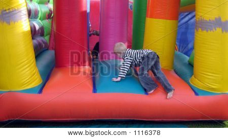 Child Playing In A Bouncy Castle