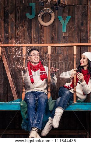 Couple in Christmas clothes playing with snow