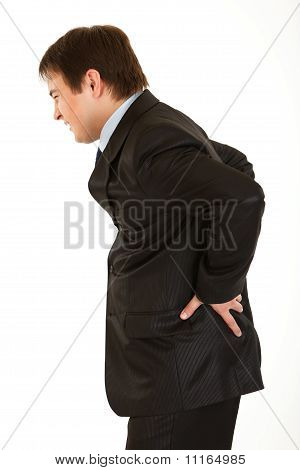Young businessman holding his hand at his aching back isolated on white