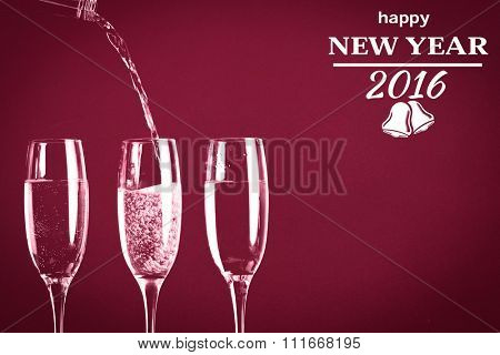happy new year message against two full glasses of champagne and one being filled