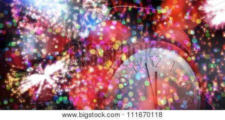 Alarm clock counting down to twelve against colourful fireworks exploding on black background