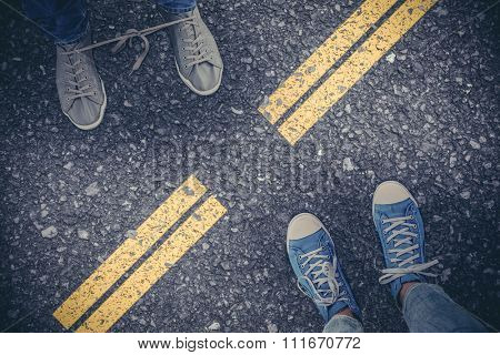 Low section of man with shoelaces tied together against road