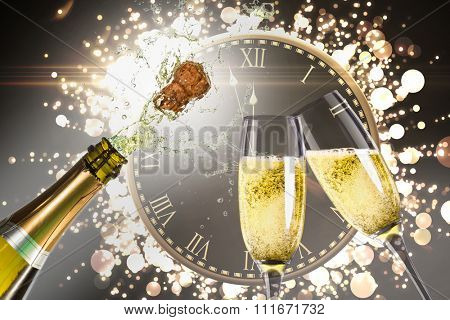 Clock counting down to midnight against champagne popping