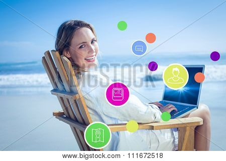 Gorgeous blonde sitting on deck chair using laptop on beach against apps
