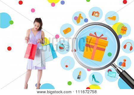 Stylish brunette in purpul dress opening shopping bag against dot pattern