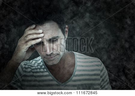 Upset man with hand on forehead against black
