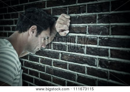Upset man leaning on white background against red brick wall