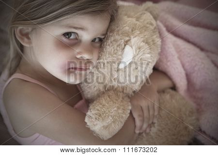 Close-up portrait of a young girl with stuffed toy at home
