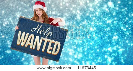 Festive redhead smiling at camera holding poster against vintage help wanted sign