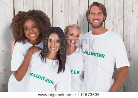 Smiling group of volunteers against wooden background