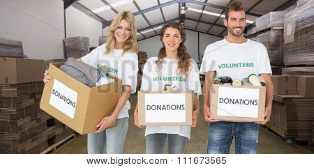 Portrait of three smiling young people with donation boxes against forklift in a large warehouse