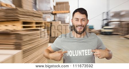 Man showing volunteer text on tshirt against cardboard boxes in warehouse