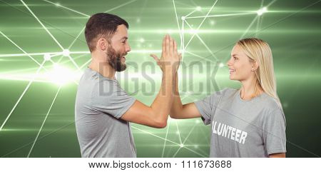 Smiling volunteer doing high five in office against glowing geometric design