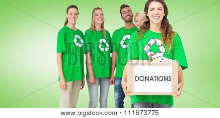 People in recycling symbol tshirts with donation box against green vignette
