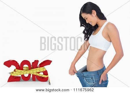 Cheerful woman holding her too big jeans against white background with vignette