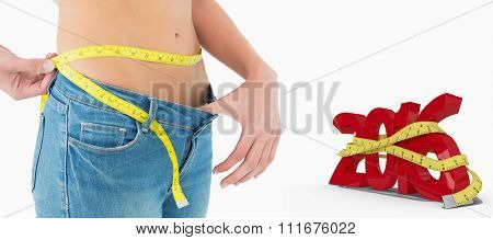 Mid section of woman measuring waist in a big sized jeans against white background with vignette