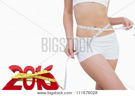 Midsection of slim woman measuring waist against white background with vignette