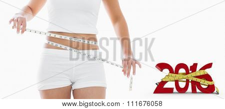 Midsection of woman measuring waist against white background with vignette