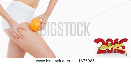 Fit woman squeezing fat on thigh as she holds orange against white background with vignette