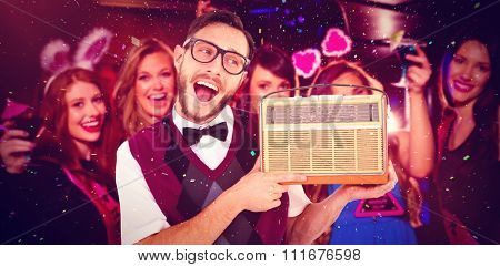 Geeky hipster holding a retro radio against pretty friends on a hen night