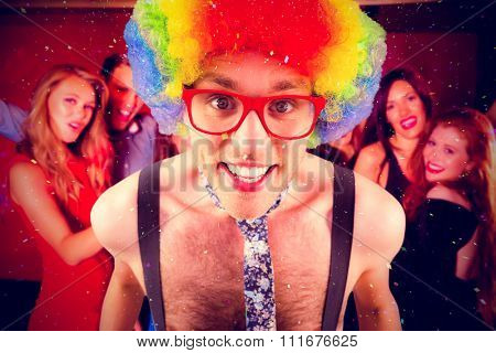 Geeky hipster in afro rainbow wig against happy friends on a night out together