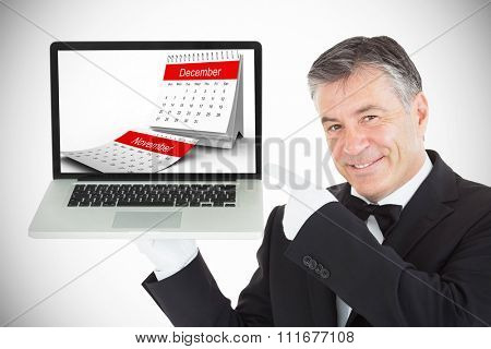 Desk calendar showing December against smiling waiter pointing us something on a laptop