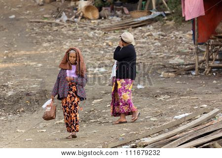 MANDALAY,MYANMAR,JANUARY 17, 2015 : A woman is carrying a bag , walking in a slum area near the river in Mandalay, Myanmar (Burma).