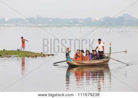 AMARAPURA, MYANMAR, JANUARY 18, 2015 : Some burmese people are proposing a sailing in wooden rowing boats on the Taungthaman lake at the U Bein bridge near Mandalay, Myanmar (Burma).