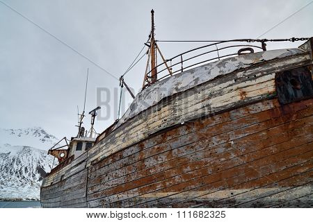 Commercial wooden fishing boat vessel in the dock in winter