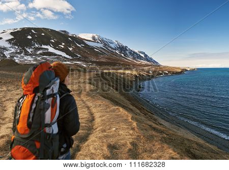 Solo independent traveler on active holiday, hiking trekking in beautiful natural outdoor landscape by the ocean and mountains