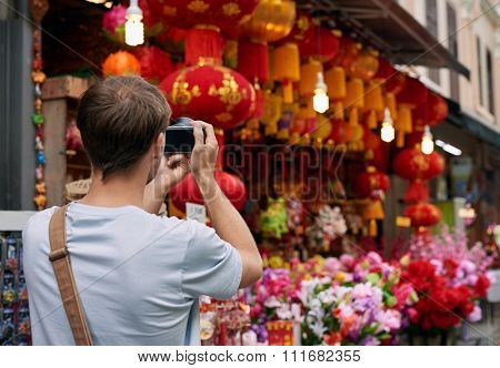 Solo traveler tourist taking photos of red colourful shop store decorations for chines new year in modern asian city
