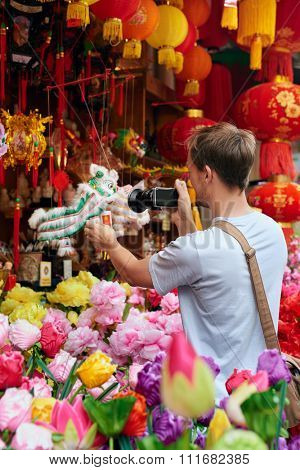 Solo traveler tourist taking photos of traditional cultural lion dance souvenir shop store decorations for chinese new year in modern asian city