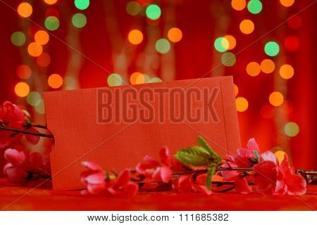 Chinese new year festival decorations, blank copy space on red packet and plum blossom on red glitter background.