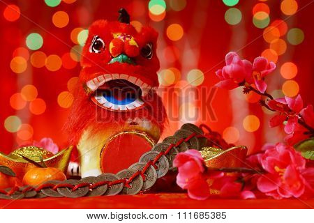 Chinese new year decorations, miniature dancing lion and ancient money on red glitter background.