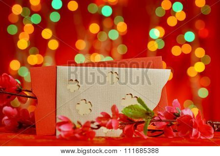 Chinese new year festival decorations, red packet and plum flower on red glitter background.