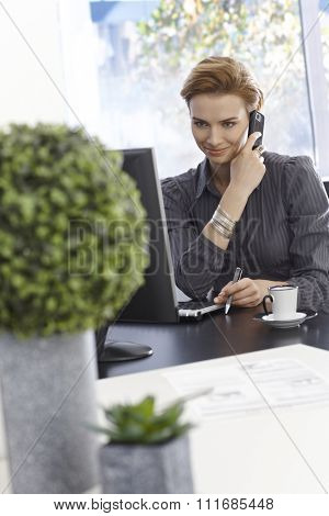 Smiling young businesswoman talking on mobilephone, sitting in green office.