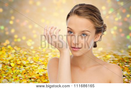 beauty, aroma, people and body care concept - young woman smelling perfume from wrist of her hand over yellow glitter and confetti background