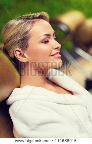 people, beauty, healthy lifestyle and relaxation concept - close up of beautiful young woman resting on chair in bath robe at spa